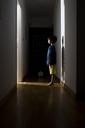 Lonely little boy standing in the corridor at home looking at open door - AZOF00001