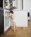 Baby boy wearing diaper exploring refrigerator in the kitchen - AZOF00004