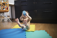 Baby boy sitting on the floor with legs in the air drinking water - AZOF00007