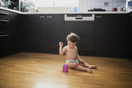Baby boy sitting on floor in the kitchen playing with plastic cup - AZOF00010