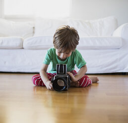 Toddler boy sitting on the floor at home using an old-fashioned film camera - AZOF00016