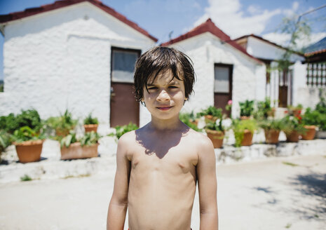 Portrait of a barechested boy standing in sunshine in front of a house - AZOF00025