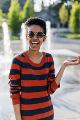 Portrait of laughing young woman wearing  sunglasses and striped pullover - GIOF04338