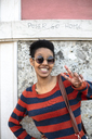 Portrait of smiling young woman wearing sunglasses and striped pullover showing victory sign - GIOF04341
