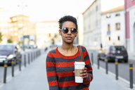 Portrait of young woman with coffee to go wearing sunglasses and striped pullover - GIOF04344