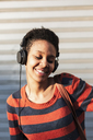 Portrait of smiling young woman listening music with headphones - GIOF04350