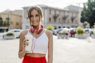 Portrait of smiling teenage girl with takeaway drink in the city - GIOF04401