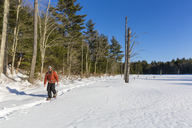 A man snowshoes across a frozen beaver pond on newly conserved land in Epping, New Hampshire. - AURF04075