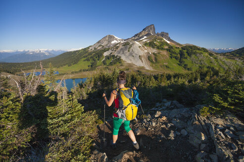 Aphotographer takes a picture of a young woman hiking on the Panorama Ridge Trail in Garibaldi Provincial Park, British Columbia, Canada. - AURF04324
