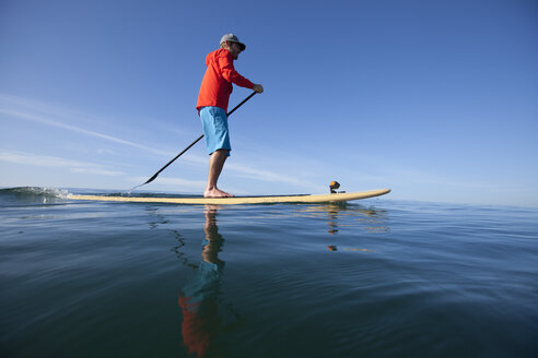 An adult man stand up paddle boarding on the ocean in calm conditions. - AURF04342