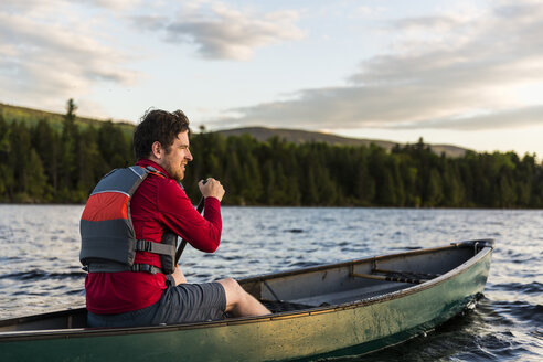 A Man Paddles His Canoe On Long Pond In Maine's North Woods Near Greenville, Maine - AURF04507
