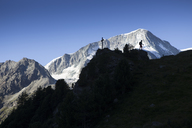 A solo male hiker is walking over a mountain ridge above Arolla in the Swiss Alps. - AURF04534