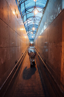 Rear view of spaceman in the city at night walking in narrow passageway - VPIF00650