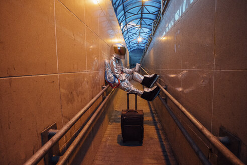 Spaceman in the city at night with rolling suitcase in narrow passageway - VPIF00659