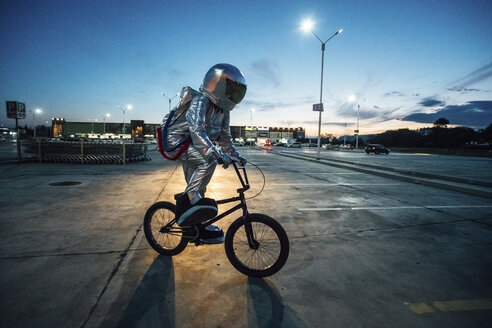 Spaceman in the city at night on parking lot riding bmx bike - VPIF00671