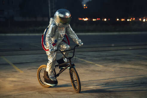 Spaceman in the city at night on parking lot riding bmx bike - VPIF00674