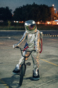 Spaceman in the city at night on parking lot with bmx bike - VPIF00677
