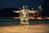 Spaceman in the city at night on parking lot inside shopping cart - VPIF00680
