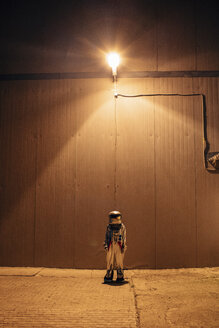 Spaceman standing under lamp at a wall at night - VPIF00692