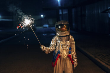 Spaceman standing outdoors at night holding sparkler - VPIF00698