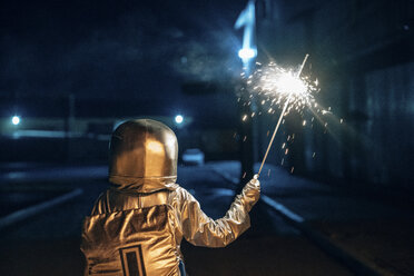 Rear view of spaceman standing outdoors at night holding sparkler - VPIF00701