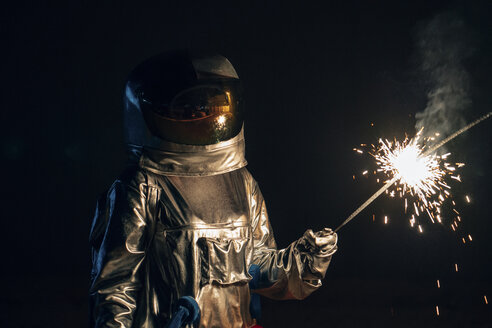 Spaceman standing outdoors at night holding sparkler - VPIF00704
