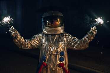 Spaceman standing on a road at night holding sparklers - VPIF00707