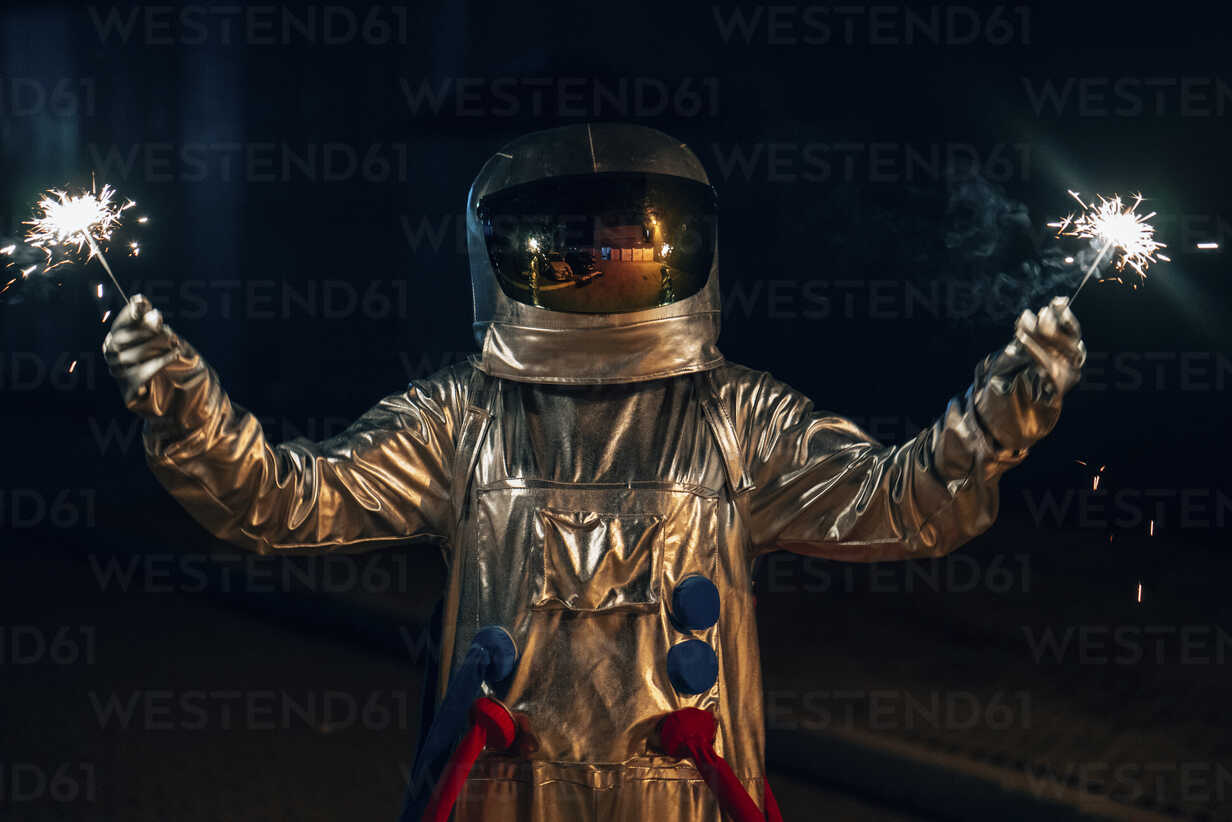 Spaceman standing on a road at night holding sparklers - VPIF00707 - Vasily Pindyurin/Westend61