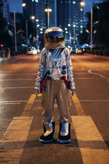 Spaceman standing on a street in the city at night - VPIF00710