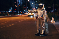Spaceman standing on a street in the city at night hitchhiking - VPIF00716