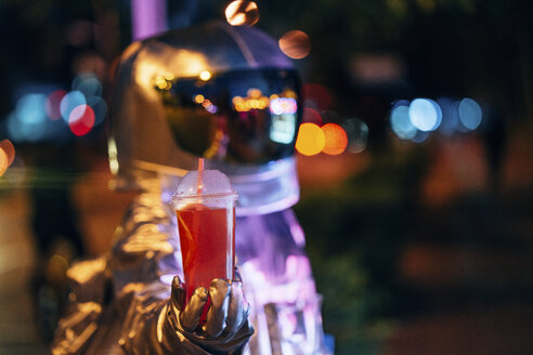 Spaceman in the city at night holding takeaway drink - VPIF00719
