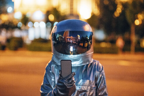 Spaceman on a street in the city at night holding smartphone - VPIF00722