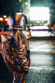 Spaceman on a street in the city at night attracted by shining projection screen - VPIF00728