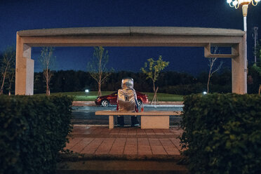 Spaceman sitting on bench at a bus stop at night - VPIF00731