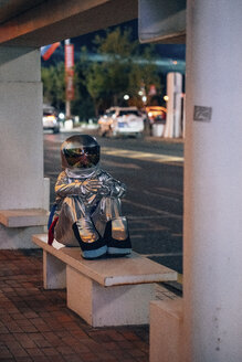 Spaceman sitting on bench at a bus stop at night - VPIF00734