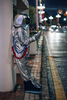Spaceman standing at a bus stop at night holding cell phone - VPIF00737