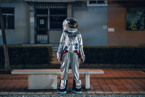 Spaceman standing at a bench in the city at night - VPIF00740
