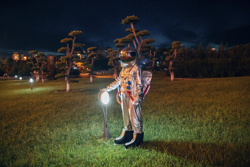 Spaceman standing at a lamp in a park at night - VPIF00743