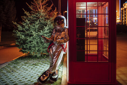 Spaceman leaning against a telephone box at night reading phone book - VPIF00746