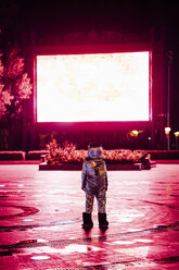 Spaceman on a square at night attracted by shining projection screen - VPIF00755