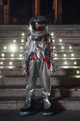 Spaceman standing at illuminated stairs at night - VPIF00758