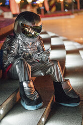 Spaceman sitting on illuminated stairs at night using cell phone - VPIF00761