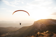 Spain, Silhouette of paraglider soaring high above the mountains at sunset - OCAF00352