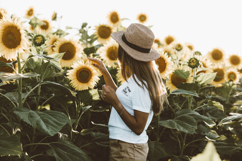 Young woman with straw hat, standing in a field of sunflowers - OCAF00358