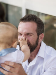 Man playing with baby girl, pinching his nose - LAF02092