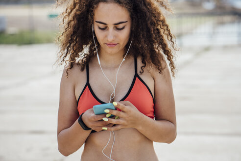 Young athletic woman wearing earbuds and using smartphone - VPIF00784