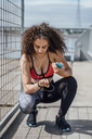 Young athletic woman with smartphone and earbuds crouching outdoors looking at wristwatch - VPIF00790