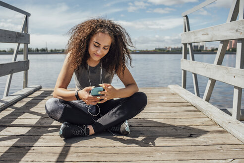 Young athletic woman sitting at the riverside using smartphone - VPIF00814