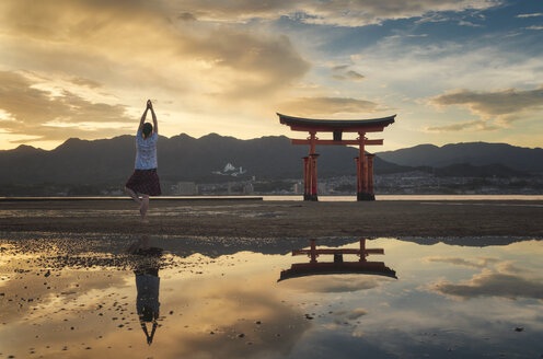 Woman enjoying the sunset on Itsukushima Island or Miyajima, Hiroshima, Japan - EPF00484