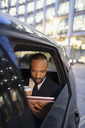 Businessman drinking coffee, using digital tablet in crowdsourced taxi - CAIF21997
